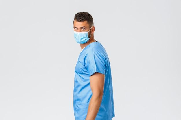 Trabalhadores de saúde, covid-19, coronavírus e prevenção do conceito de vírus. belo médico hispânico, enfermeiro com máscara médica lutando contra a pandemia, volte para olhar para a câmera sério e determinado