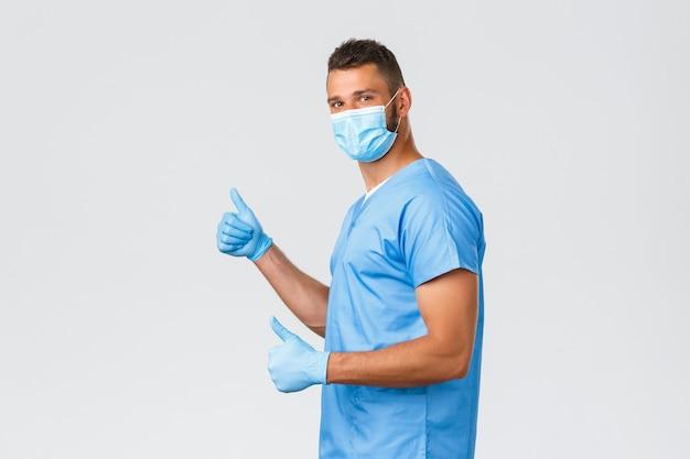 Trabalhadores de saúde, covid-19, coronavírus e prevenção do conceito de vírus. médico, enfermeiro ou estagiário otimista e alegre, usando uniforme, luvas e máscara médica, mostrando o polegar para cima em apoio ou aprovação