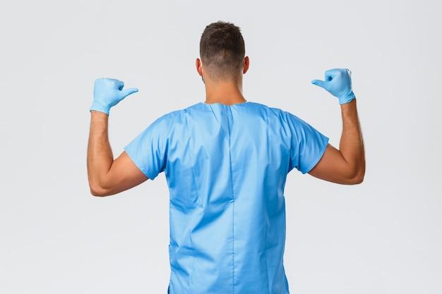 Trabalhadores de saúde, covid-19, coronavírus e prevenção do conceito de vírus. médicos super-heróis. dorso de médico ou enfermeiro em uniforme azul, médico apontando para trás, sendo forte durante a pandemia