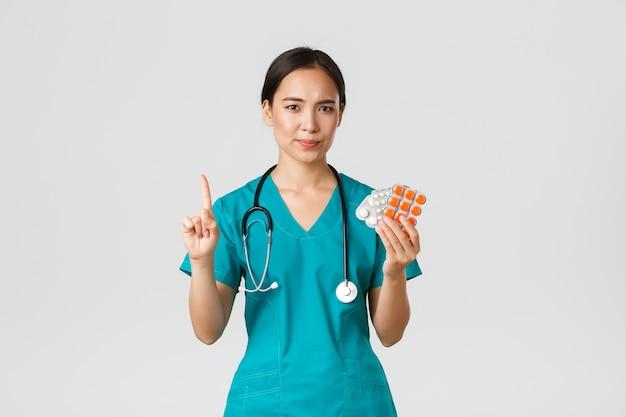 Trabalhadores de saúde, prevenção de vírus, conceito de campanha de quarentena. médica asiática relutante e decepcionada, médica balançando o dedo em desaprovação, repreendendo o paciente por tomar medicamentos