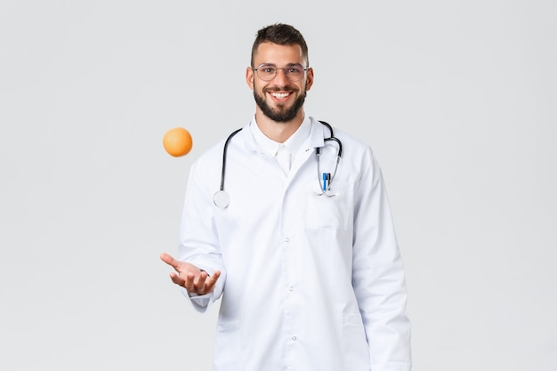 Trabalhadores de saúde, seguro médico, laboratório clínico e conceito covid-19. médico hispânico sorridente e alegre, médico de jaleco branco, jogar laranja, recomendar comer frutas com vitaminas saudáveis