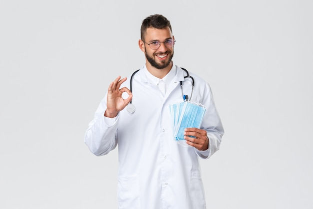 Trabalhadores de saúde, seguro médico, pandemia e conceito covid-19. médico hispânico simpático de jaleco branco, estetoscópio, garantia de boa qualidade do epi, conselho uso de máscaras médicas durante coronavírus