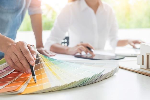 Trabalhadores de trabalho criativos ou de designers de interiores com tela de pantone e planos de construção na mesa de escritório, arquitetos escolhendo amostras de cores para projeto de projeto