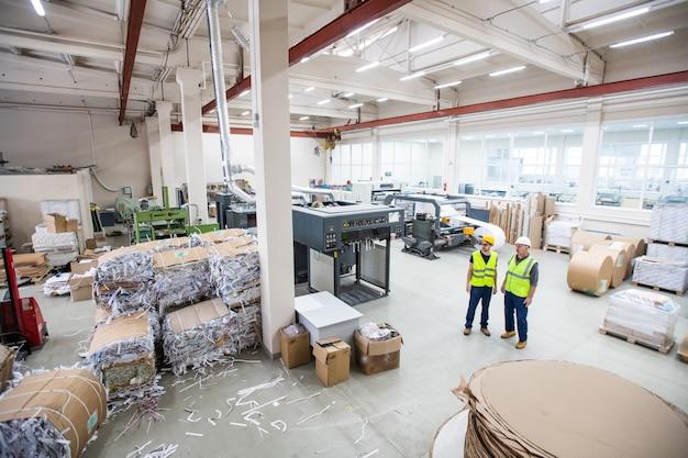 Trabalhadores de uma fábrica de reciclagem de papel usando coletes reflexivos em pé na loja com papéis embalados em máquinas de desenho e corte