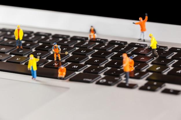 Trabalhadores diminutos que reparam um teclado de laptop