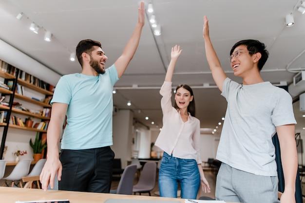 Trabalhadores diversos e felizes cooperando em equipe no escritório