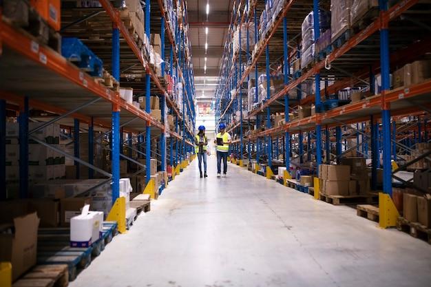 Trabalhadores do armazém caminhando na área de armazenamento da grande fábrica.