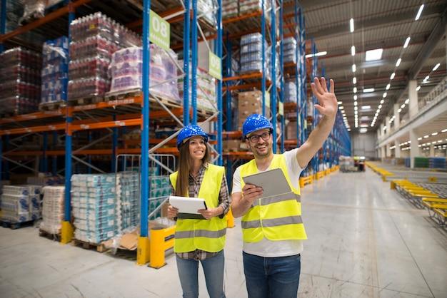 Trabalhadores do armazém verificando a organização e distribuição de produtos em grande área de armazenamento