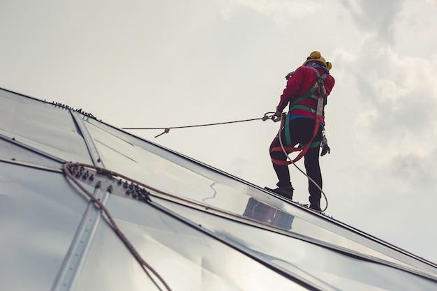 Trabalhadores do sexo masculino com segurança de altura de acesso por corda conectando-se com cúpula do tanque de óleo de arnês de segurança de oito nós