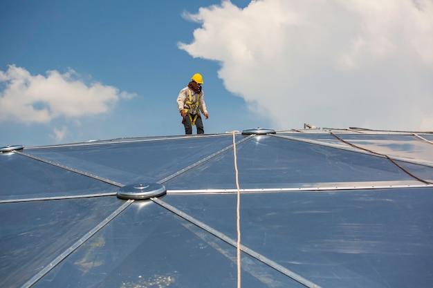 Trabalhadores do sexo masculino com segurança de altura de acesso por corda conectando-se com um arnês de segurança de nó, fixando-se em sistemas de ponto de ancoragem de contenção de queda do telhado e prontos para subir, cúpula do tanque de óleo do local de construção