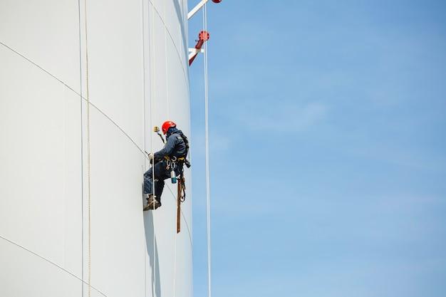 Trabalhadores do sexo masculino controlam a inspeção de acesso por corda ao tanque de altura de corda para baixo do trabalho de segurança do tanque de armazenamento de placa de concha de espessura em altura.