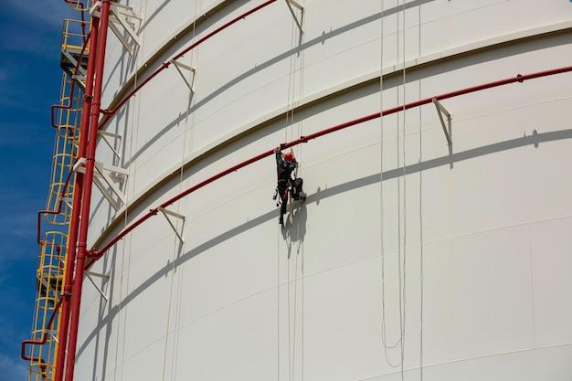 Trabalhadores do sexo masculino controlam o balanço da corda para baixo, inspeção do acesso à corda do tanque de altura do gasoduto de espessura e o céu azul do fundo do gás do tanque.