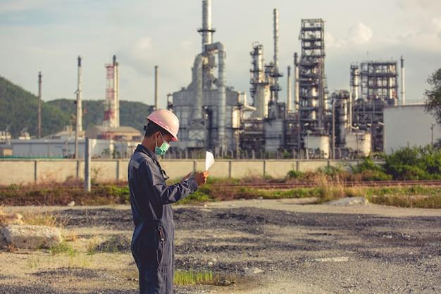 Trabalhadores do sexo masculino fazem a inspeção e registram o processo de refinaria no canteiro de obras industriais de óleo e gás.