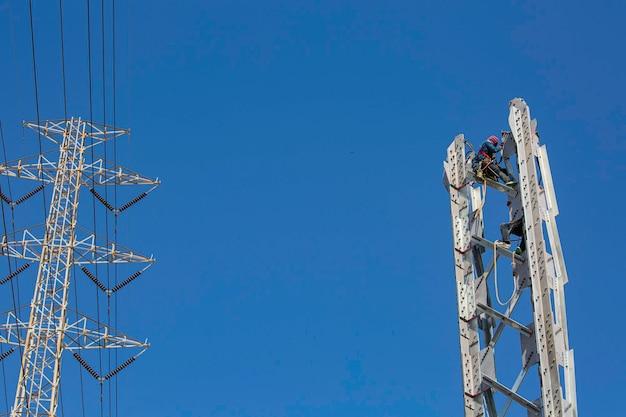 Trabalhadores do sexo masculino instalação de postes de transmissão de energia elétrica de alta tensão na coluna em linha de aço em risco de altura