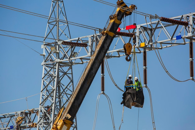 Trabalhadores do sexo masculino instalação de postes de transmissão de energia elétrica de alta tensão no guindaste trabalho em risco de altura
