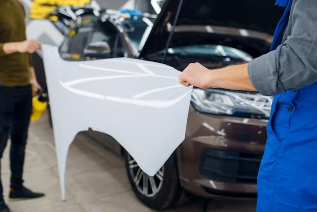 Trabalhadores do sexo masculino mantém o modelo do pára-choque dianteiro do filme de proteção do carro. instalação de revestimento que protege a pintura do automóvel de arranhões. novo veículo na garagem, procedimento de ajuste