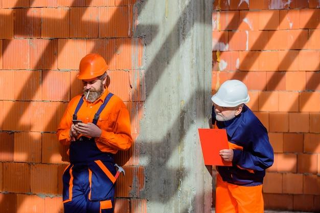 Trabalhadores em capacete dois reparador em construção publicitária reparador chaves de boca de martelo
