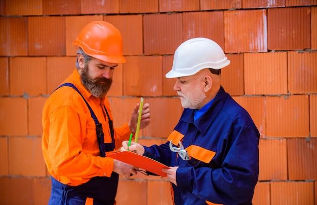 Trabalhadores em dois reparadores de capacete em construção anunciando construtor de reparadores em capacete de construção