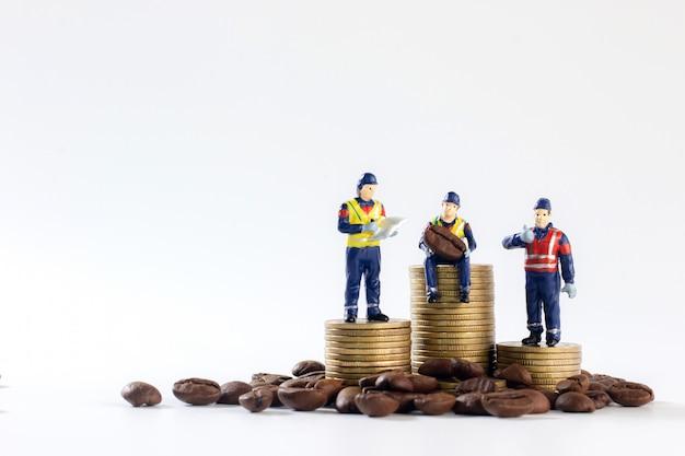 Trabalhadores em miniatura estão sentados e de pé sobre uma pilha de moedas de ouro e abaixo tem grãos de café, isolados no branco
