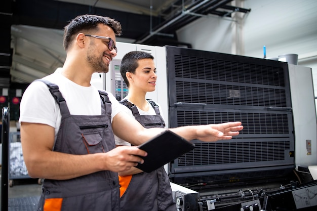Trabalhadores em pé ao lado da máquina de impressão offset e controlando o processo de impressão.