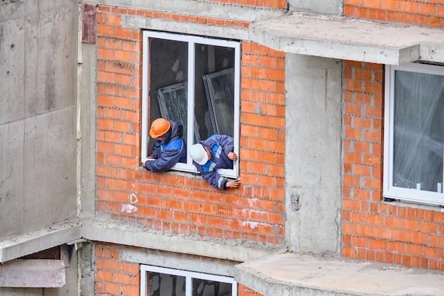 Trabalhadores em um canteiro de obras instalam janelas em um prédio residencial