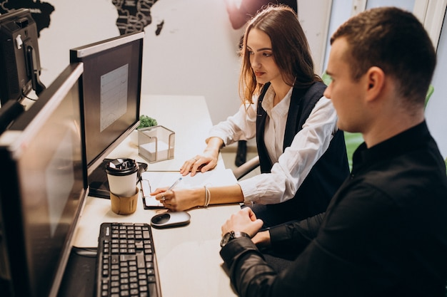 Trabalhadores em uma empresa de ti trabalhando em um computador