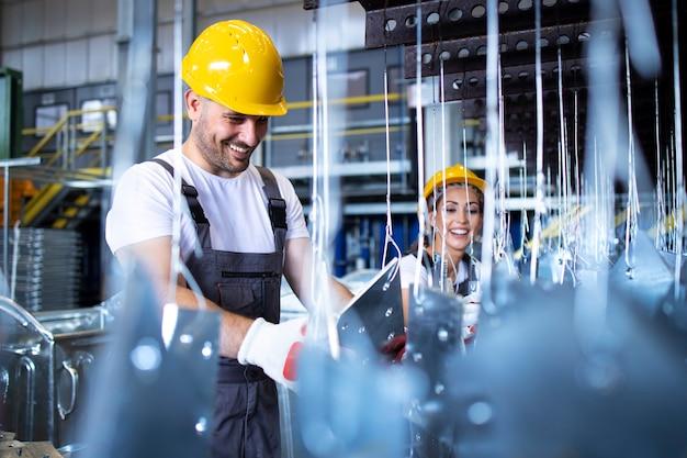 Trabalhadores em uniformes e capacetes de proteção amarelos trabalhando na fábrica