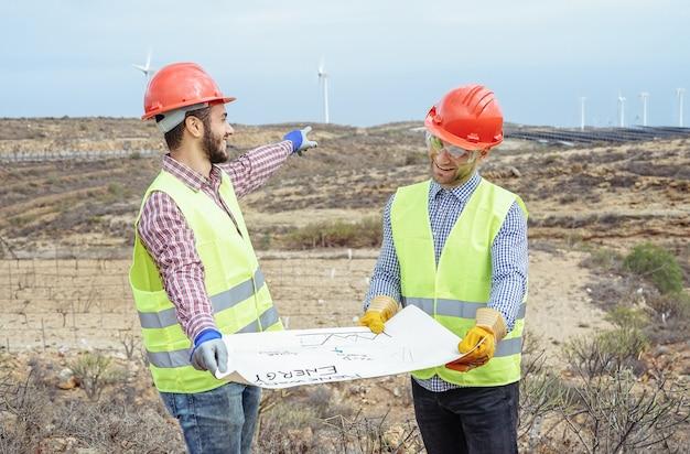 Trabalhadores engenheiros lendo e conversando sobre o novo projeto de energia renovável