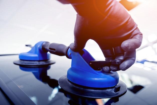 Trabalhadores especiais de automóveis substituindo pára-brisas ou pára-brisas de um carro na garagem da estação de serviço automóvel.