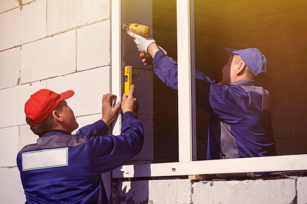 Trabalhadores especializados instalam janelas de plástico, reparos de edifícios residenciais