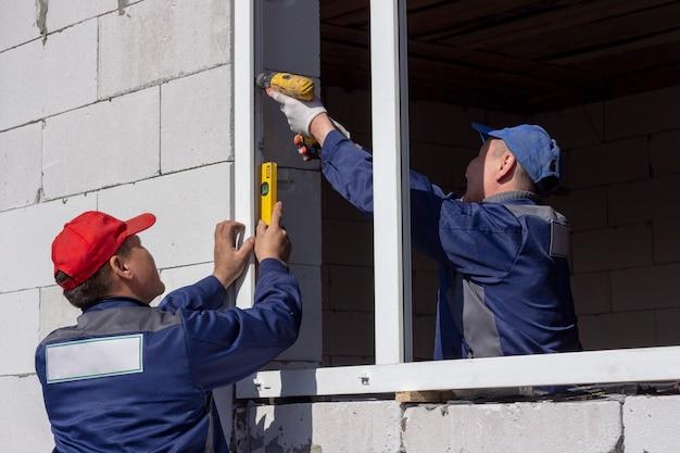Trabalhadores especializados instalam janelas de plástico, reparos de edifícios