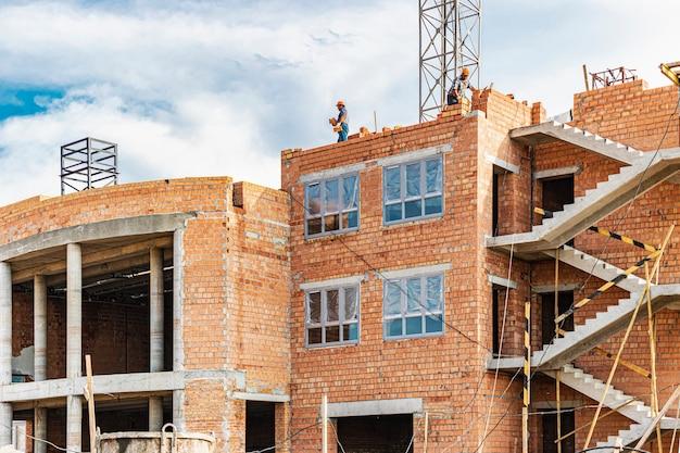 Trabalhadores estão colocando a parede de um prédio feito de tijolos de cerâmica vermelha. construção de edifício alto monolítico com paredes de tijolos.
