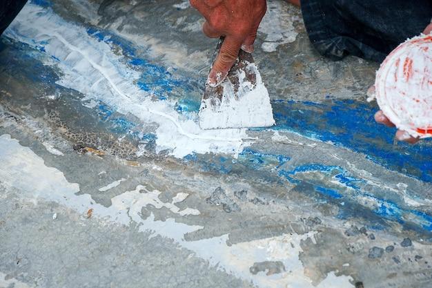 Trabalhadores estão consertando rachaduras no piso espalhando gesso com espátula reparando deck impermeabilizante