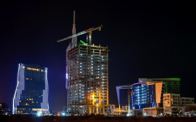 Trabalhadores estão construindo belos edifícios mesmo à noite.