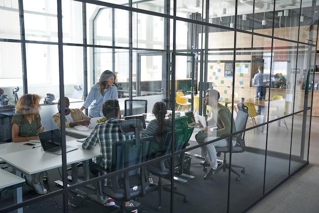 Trabalhadores falando sobre relatório financeiro da empresa