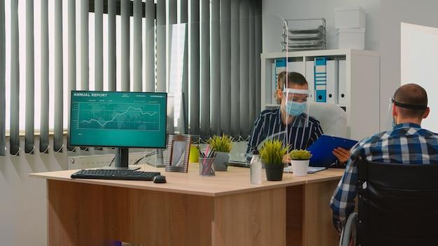 Trabalhadores falando usando máscaras de proteção no novo escritório normal durante o coronavírus, empresário se movendo com cadeira de rodas. homem imobilizado e colega de trabalho em empresa corporativa respeitando a distância social.