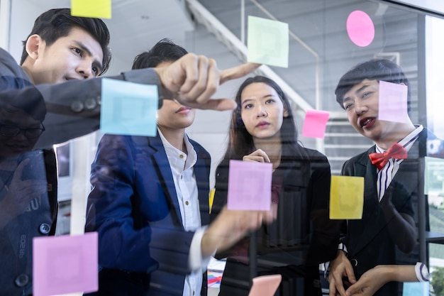 Trabalhadores felizes e bem-sucedidos grupo de empresários asiáticos com gêneros diversos (lgbt) e usa notas de post-it para compartilhar ideias. conceito de brainstorming. nota adesiva na parede de vidro da sala de reuniões do escritório