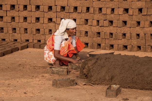 Trabalhadores indianos processando argila ou lama e fabricando tijolos tradicionais à mão no forno de tijolos, na fábrica ou no campo.