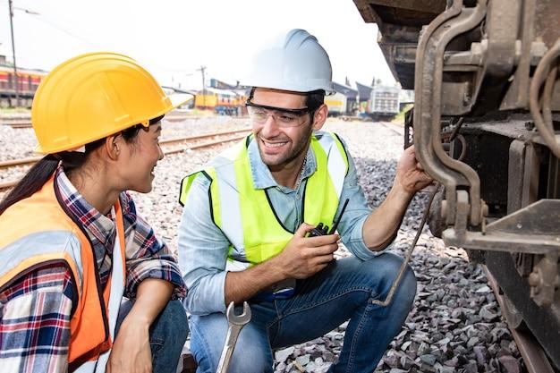 Trabalhadores industriais assistentes discutindo motores na estação de trem