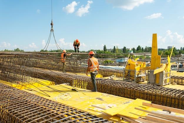 Trabalhadores instalam estruturas de reforço durante a construção de uma ponte de transporte