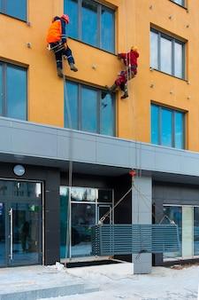 Trabalhadores instalam nichos para condicionadores de ar na casa em construção