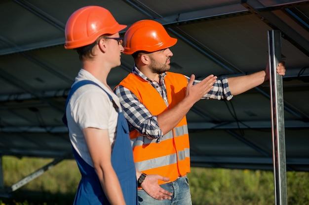 Trabalhadores instalando painéis fotovoltaicos na estação de energia solar.
