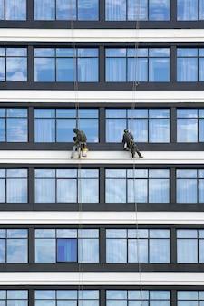 Trabalhadores limpam as janelas dos arranha-céus.