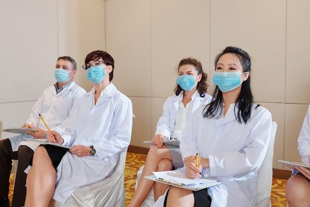 Trabalhadores médicos com máscaras de proteção e jalecos ouvindo o palestrante