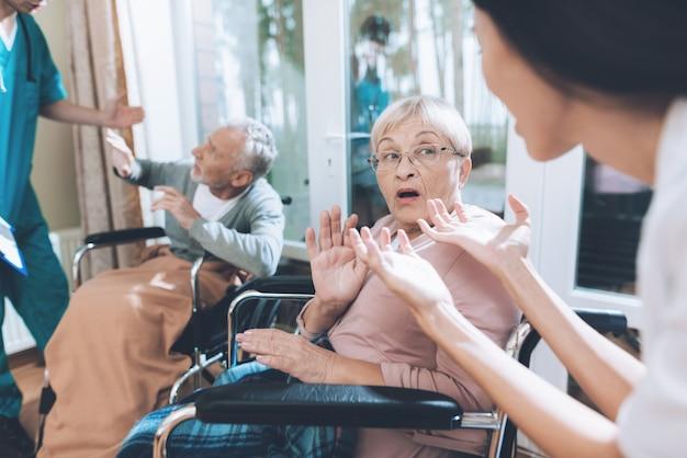 Trabalhadores médicos discutem com um casal de idosos.