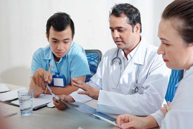 Trabalhadores médicos discutindo raio-x de pulmão