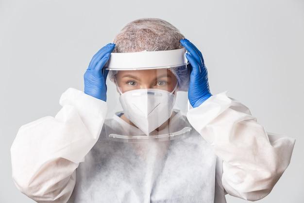 Trabalhadores médicos, pandemia de covid-19, conceito de coronavírus. close-up esperançosa médica sorridente vestiu equipamento de proteção individual antes de entrar na zona contagiosa com pessoas doentes, consertando a máscara facial.