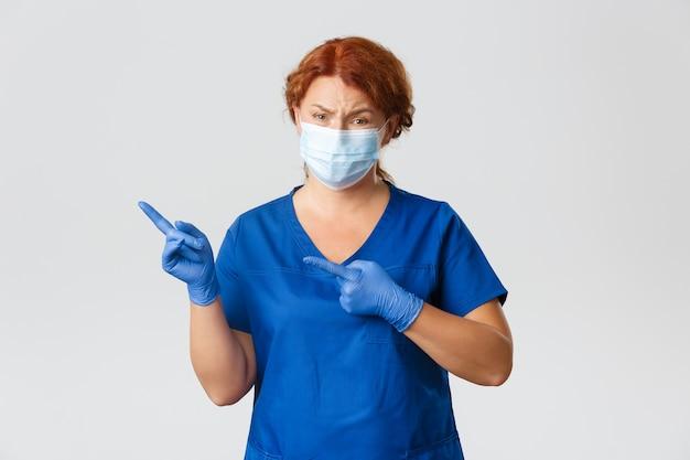 Trabalhadores médicos, pandemia de covid-19, conceito de coronavírus. médica ruiva cética e pouco divertida, médica olhando com julgamento, apontando algo inexpressivo no canto superior esquerdo, use máscara.