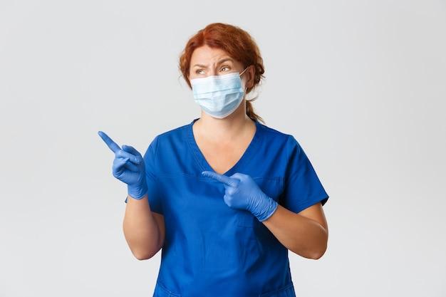 Trabalhadores médicos, pandemia de covid-19, conceito de coronavírus. médica ruiva, cética e pouco divertida, médica parecendo com aversão, apontando para o canto superior esquerdo algo inexpressivo, usar máscara.