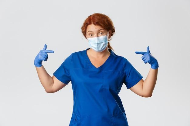 Trabalhadores médicos, pandemia de covid-19, conceito de coronavírus. profissional e atrevida médica, enfermeira na máscara facial e luvas, apontando para si mesma com olhar confiante, sendo profissional, plano de fundo cinza.